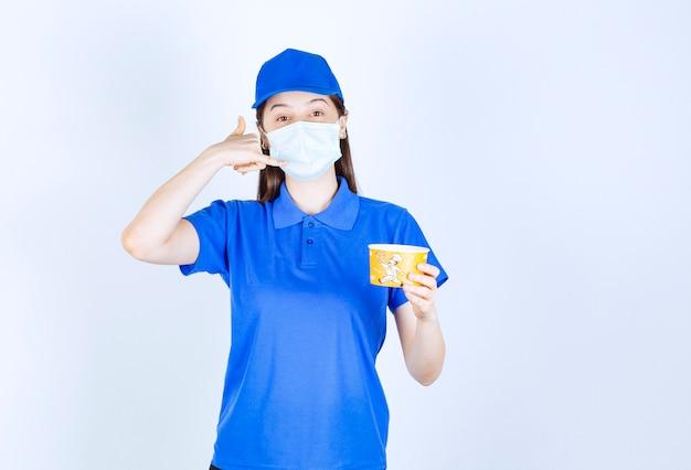 Jonge vrouw in uniform en medisch masker met plastic beker die een telefoongebaar maakt