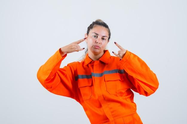 Jonge vrouw in uniform werknemer doet rock in roll-symbool met handen omhoog en op zoek naar verzekerd, vooraanzicht.
