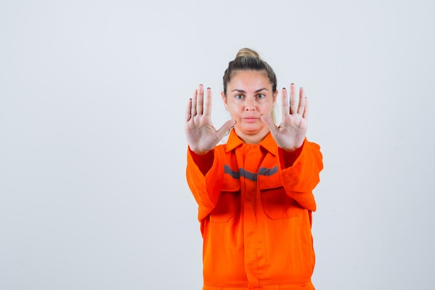 Jonge vrouw in uniform werknemer met stop gebaar, vooraanzicht.
