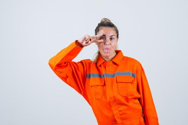 Jonge vrouw in uniform werknemer tonen v-teken over haar oog terwijl ze tong uitsteekt en er grappig uitziet, vooraanzicht.