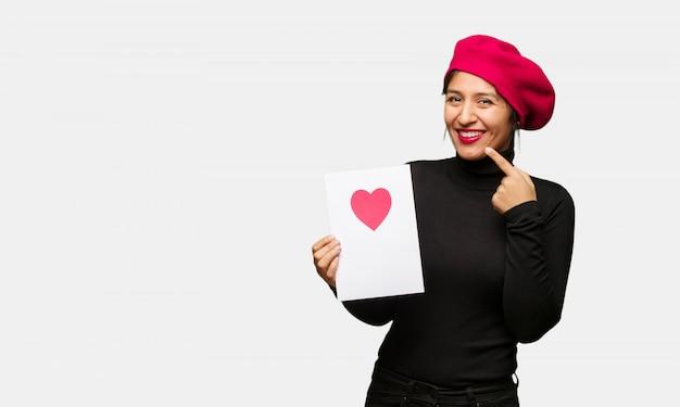 Jonge vrouw in valentijnsdag glimlacht, wijzende mond
