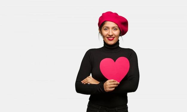 Jonge vrouw in valentijnsdag overschrijding van wapens, glimlachend en ontspannen