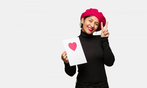 Jonge vrouw in valentijnsdag plezier en gelukkig een gebaar van de overwinning te doen