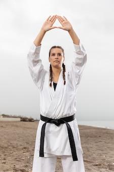 Jonge vrouw in vechtsportenkostuum