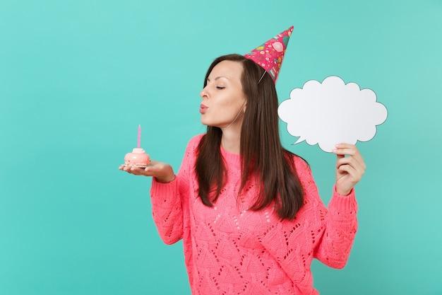 Jonge vrouw in verjaardagshoed die kaars op taart uitblaast, lege blanco houdt say cloud, tekstballon voor promotionele inhoud geïsoleerd op blauwe achtergrond. mensen levensstijl concept. bespotten kopie ruimte.