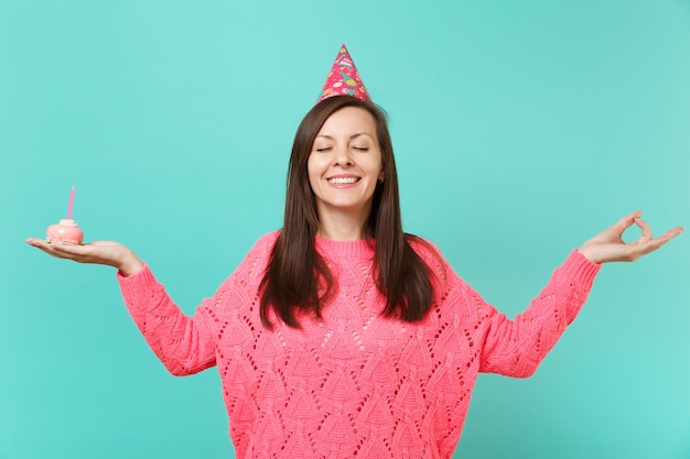 Jonge vrouw in verjaardagshoed met gesloten ogen houdt handen vast in yogagebaar, ontspannend mediteren met cake met kaars geïsoleerd op blauwe muurachtergrond. mensen levensstijl concept. bespotten kopie ruimte.