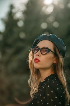 Jonge vrouw in vintage zwarte polka dot jurk buiten poseren