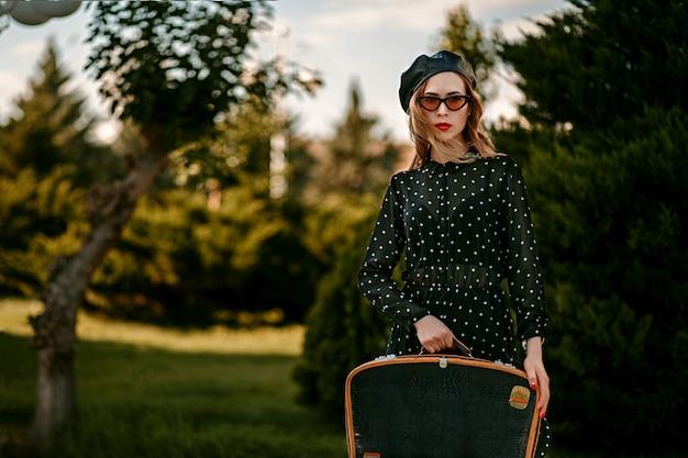 Jonge vrouw in vintage zwarte polka dot jurk met retro koffer in de hand poseren buiten