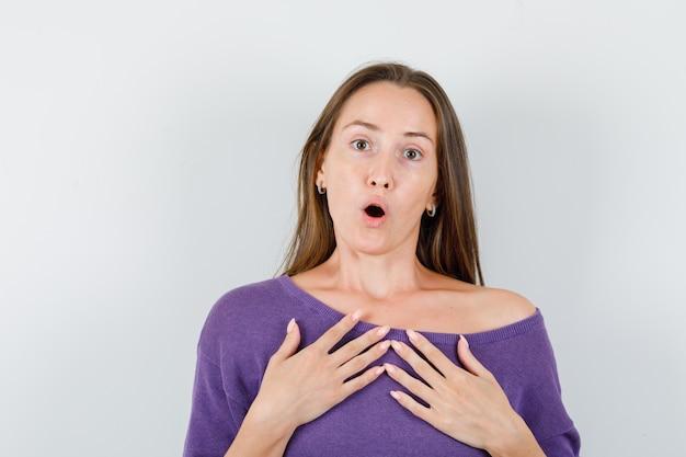 Jonge vrouw in violet overhemd hand in hand op de borst en op zoek verrast, vooraanzicht.