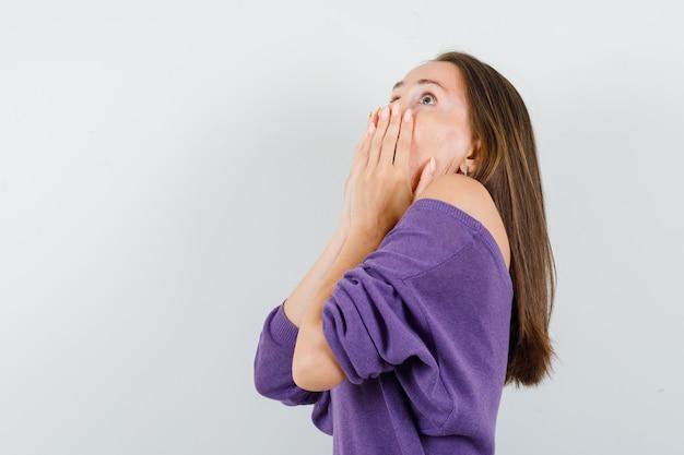 Jonge vrouw in violet overhemd hand in hand op de mond en bang op zoek.