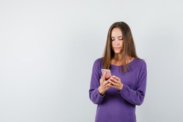 Jonge vrouw in violet overhemd met behulp van mobiele telefoon en op zoek naar druk, vooraanzicht.