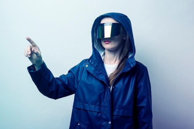 Jonge vrouw in virtual reality-bril die met een vinger op een touchscreen op een lichte achtergrond drukt.