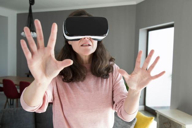 Jonge vrouw in virtuele werkelijkheidsbeschermende brillen die online spel spelen