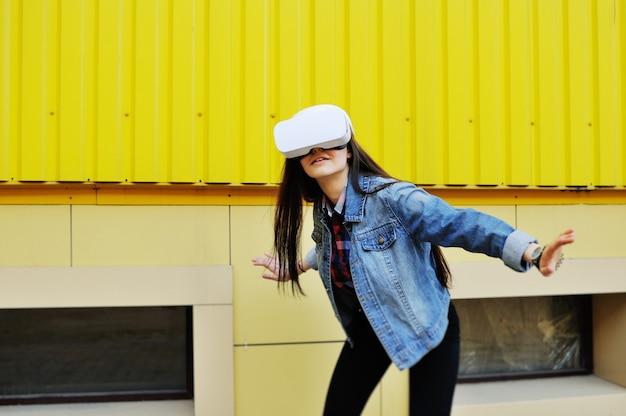 Jonge vrouw in virtuele werkelijkheidsglazen in denimjasje op gele muuroppervlakte