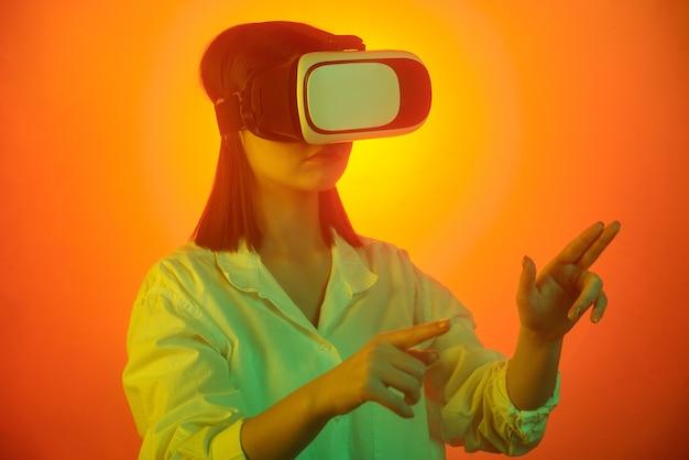 Jonge vrouw in vr-headset wijzend op virtueel display tijdens het voorbereiden van de presentatie