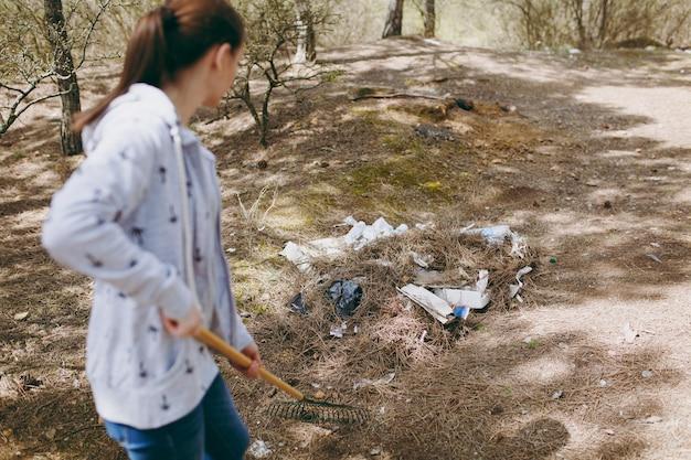 Jonge vrouw in vrijetijdskleding die afval schoonmaakt met een hark voor het ophalen van afval in een bezaaid park of bos