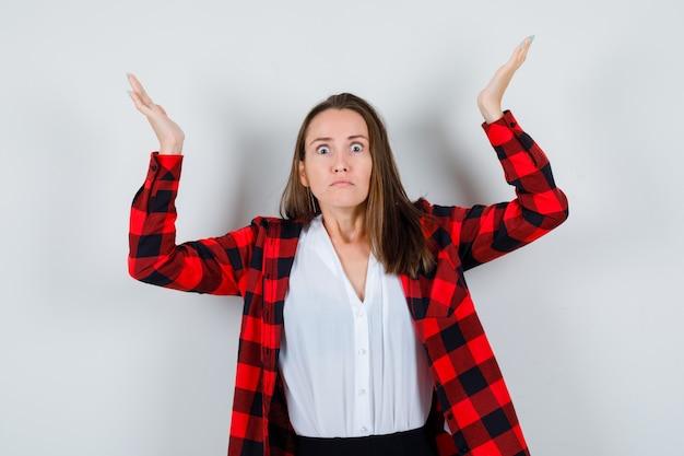 Jonge vrouw in vrijetijdskleding die armen en handen opheft en boos kijkt, vooraanzicht.