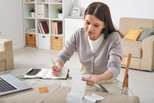 Jonge vrouw in vrijetijdskleding die betalingsbewijzen bekijkt en de aantallen in notitieboekje opschrijft