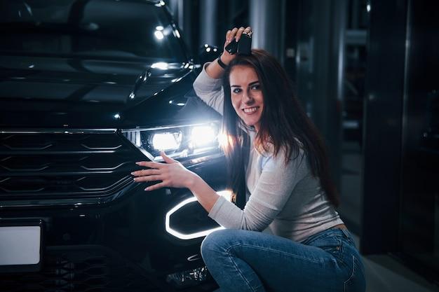 Jonge vrouw in vrijetijdskleding die dichtbij moderne zwarte auto met sleutels in handen situeert.