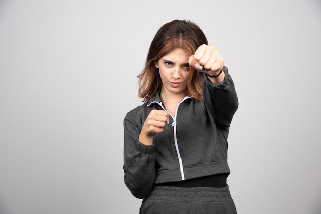 Jonge vrouw in vrijetijdskleding die haar handgemaakte punch toont.