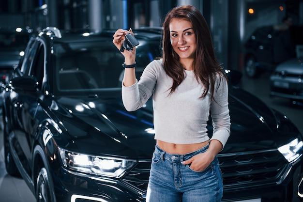 Jonge vrouw in vrijetijdskleding die zich dichtbij moderne zwarte auto met sleutels in handen bevindt.