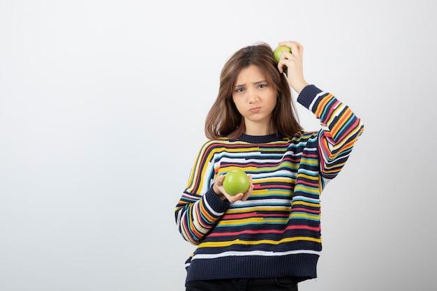 Jonge vrouw in vrijetijdskleding die zich met groene appels op witte achtergrond bevindt.