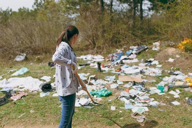 Jonge vrouw in vrijetijdskleding en latexhandschoenen voor het schoonmaken met hark voor afvalinzameling in bezaaid park