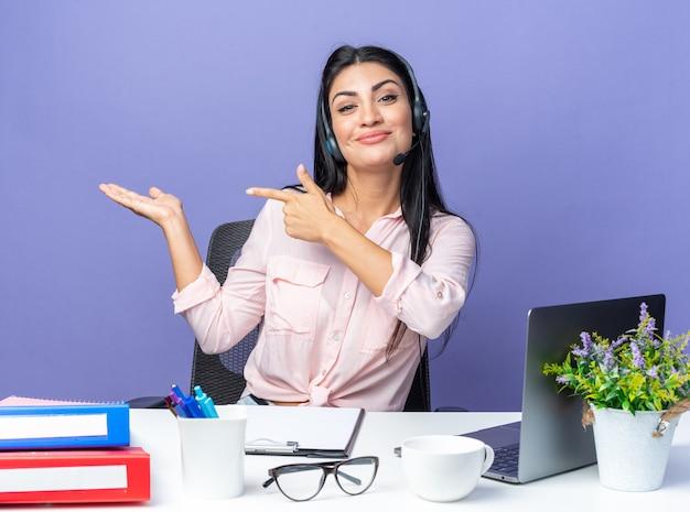 Jonge vrouw in vrijetijdskleding met een headset die lacht en met wijsvingers naar de zijkant wijst terwijl ze aan de tafel zit met een laptop