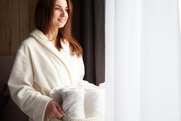 Jonge vrouw in warme badjas staat in de buurt van raam en houdt mandje met opgerolde witte handdoeken. frisheid van gewassen linnen. natuurlijk textiel. spik en span concept. goed geordend.