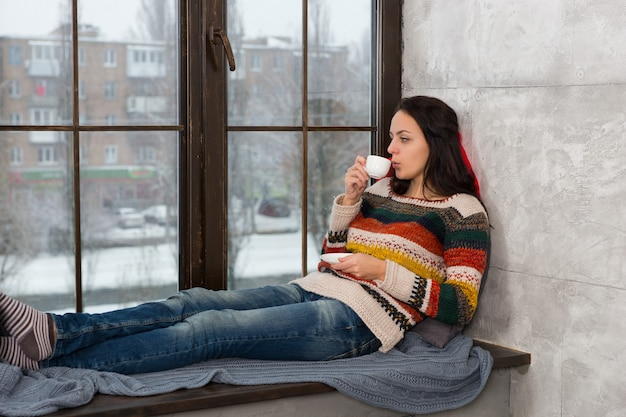 Jonge vrouw in warme gebreide trui liggend op de kussens op de vensterbank en een kopje koffie drinken