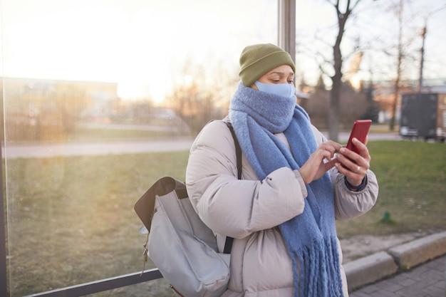 Jonge vrouw in warme kleding en in masker een bericht aan het typen op haar mobiele telefoon tijdens het wachten op de bus