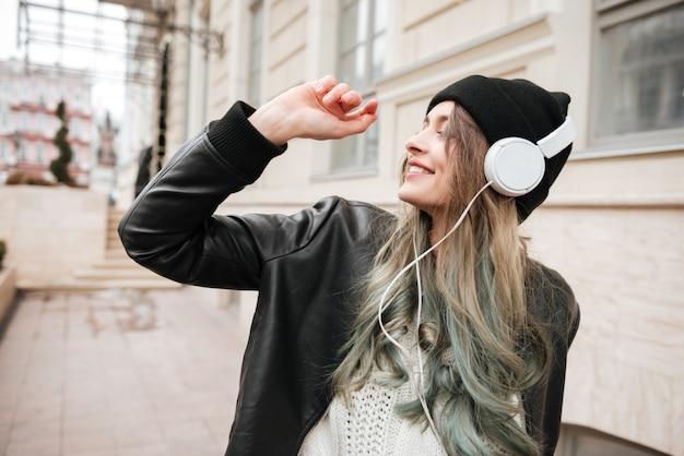 Jonge vrouw in warme kleren dansen op straat