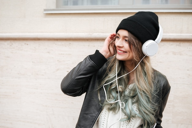 Jonge vrouw in warme kleren luisteren muziek op straat