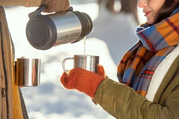 Jonge vrouw in warme winterkleding die een metalen mok vasthoudt terwijl haar man hete thee uit een thermoskan giet voor de camera tegen sneeuw