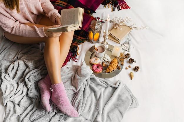 Jonge vrouw in warme wollen kleding zit op haar bed in zonnig huis
