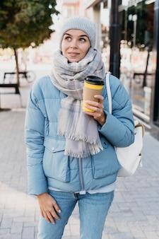 Jonge vrouw in winterkleren buitenshuis