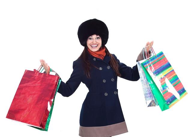 Jonge vrouw in winterkleren met boodschappentassen. geïsoleerd op een witte achtergrond