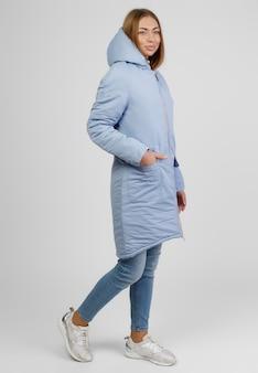 Jonge vrouw in winterkleren op witte achtergrond. fotoconcept voor reclame voor een donsjack