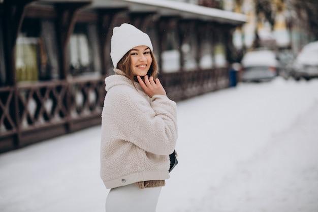 Jonge vrouw in winteroutfit buiten de straat