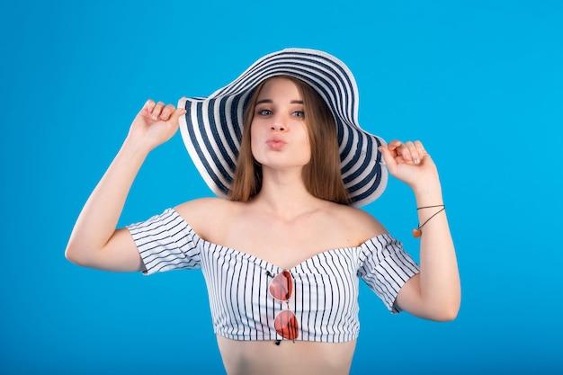 Jonge vrouw in wit gestreepte zwempaklingerie en gestreepte hoed die op blauw wordt geïsoleerd