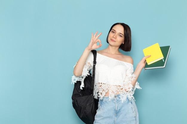 Jonge vrouw in wit overhemd, blauwe jeans en zwarte tas met copybooks lachend op blauw