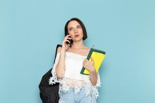 Jonge vrouw in wit overhemd, blauwe spijkerbroek en zwarte tas met copybooks praten over de telefoon op blauw