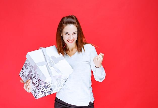 Jonge vrouw in wit overhemd die een bedrukte geschenkdoos vasthoudt en een positief handteken toont