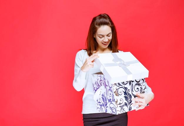 Jonge vrouw in wit overhemd die een bedrukte geschenkdoos vasthoudt, opent en verrast wordt