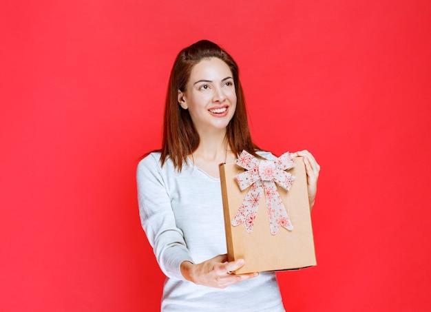 Jonge vrouw in wit overhemd die een kartonnen geschenkdoos vasthoudt en aan iemand presenteert