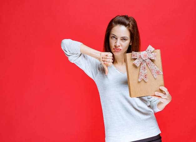 Jonge vrouw in wit overhemd die een kartonnen geschenkdoos vasthoudt en duim naar beneden laat zien