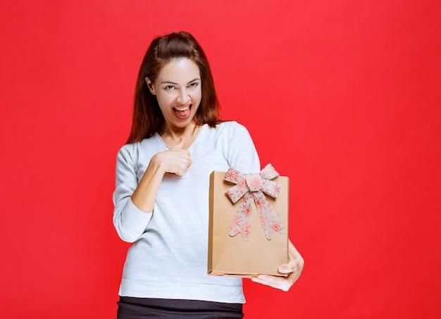 Jonge vrouw in wit overhemd die een kartonnen geschenkdoos vasthoudt en een positief handteken toont