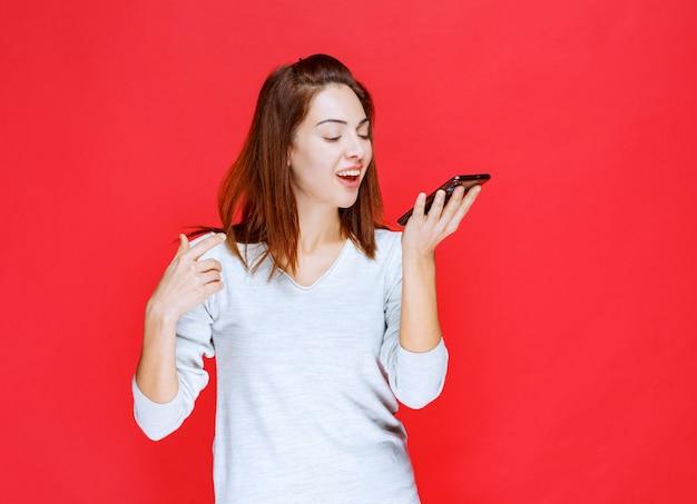 Jonge vrouw in wit overhemd die een nieuwe model smartphone vasthoudt en een videogesprek voert of haar selfie neemt
