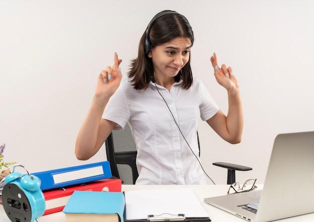 Jonge vrouw in wit overhemd en koptelefoon met een microfoon zittend aan de tafel met mappen kijken naar haar laptopscherm op videogesprek wenselijke wens kruising vingers over witte muur maken