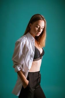 Jonge vrouw in wit overhemd en zwarte lingerie poseren